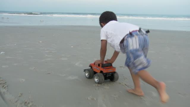 WS TS SLO MO Boy (2-3) pushing his toy jeep down beach / Jacksonville, Florida, USA