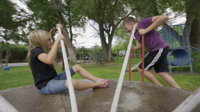boy pushing sister on neighborhood playground merry-go-round / provo, utah, united states - provo stock-videos und b-roll-filmmaterial