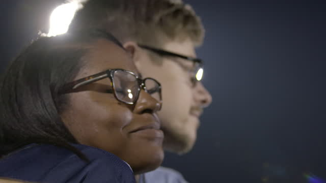 CU SLO MO. Boy puts his arm around girl and hugs her under stadium lights at sporting event.