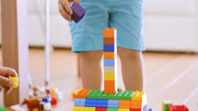 boy putting a plastic brick on the tower he made - tower stock videos & royalty-free footage