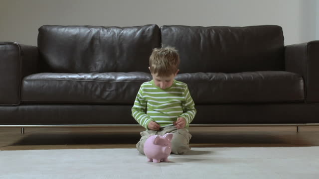 MS Boy (2-3) putting coins in piggy-bank / London, UK