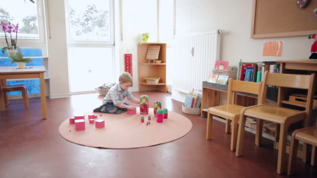 MS DS Boy putting cube on pink tower beside Russian wooden doll / Potsdam, Brandenburg, Germany