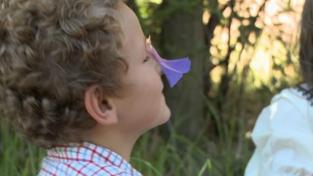 boy putting flower on face and making girl laugh - människonäsa bildbanksvideor och videomaterial från bakom kulisserna