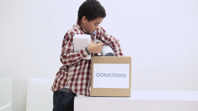 boy putting food in donation box - charitable donation stock videos & royalty-free footage