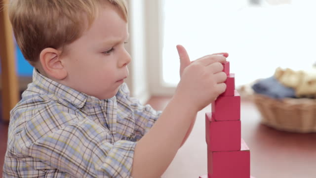ms td boy putting last cube on pink tower / potsdam, brandenburg, germany - last stock videos & royalty-free footage
