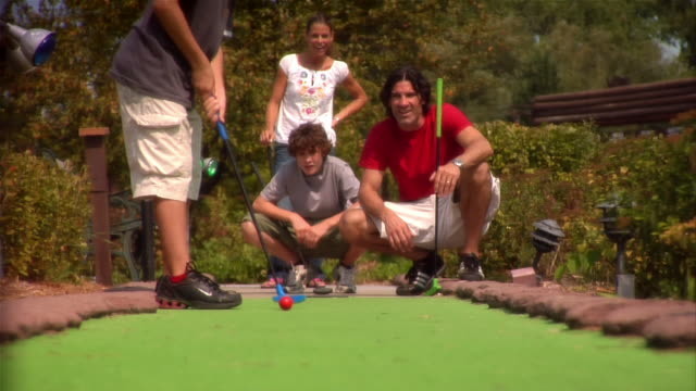 boy putting on mini golf course as family watches / family celebrating after boy makes shot - minigolf stock-videos und b-roll-filmmaterial