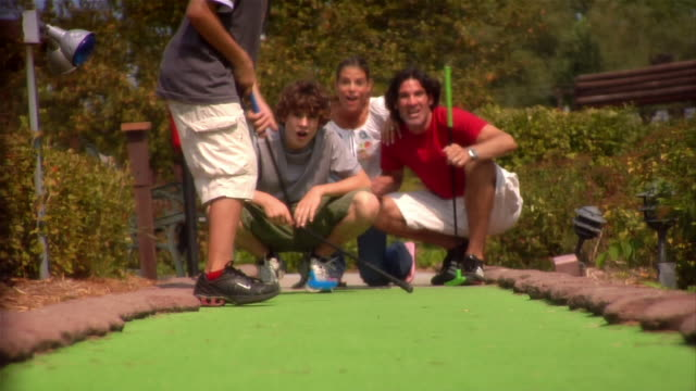 boy putting on mini golf course as family watches / family jumping up and down and hugging boy after he makes shot / entire family turning around to face camera - minigolf stock-videos und b-roll-filmmaterial
