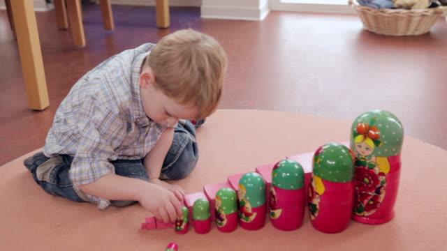 ms boy putting russian wooden dolls beside pink cubes / potsdam, brandenburg, germany - parallele geometrie stock-videos und b-roll-filmmaterial