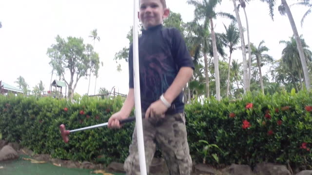 boy putts ball into mini golf hole at tourist resort then we follow him to the next hole. - kelly mason videos stock-videos und b-roll-filmmaterial