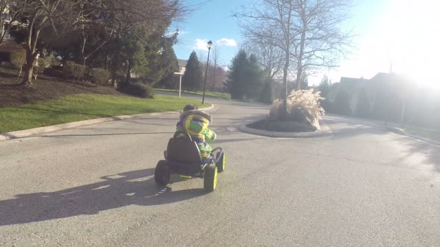 Boy races down the street in his go cart and comes to a precision stop.