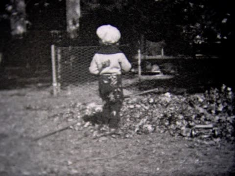 1933 boy rakes leaves. fills wheel barrow