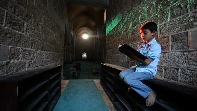 a boy read the quran in a mosque of gaza on june 4 2017 islam's holy month of ramadan is celebrated by muslims worldwide marked by fasting abstaining... - eid mubarak stock videos & royalty-free footage