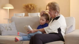 Boy reading a book with grandmom