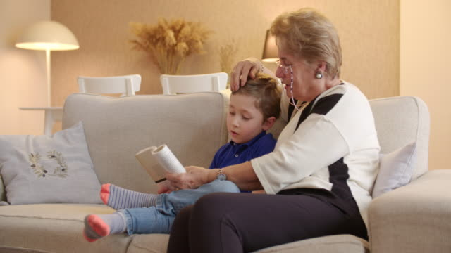boy reading a book with grandmom - serene people stock videos & royalty-free footage