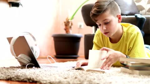 junge lesen buch in seinem zimmer - lesen stock-videos und b-roll-filmmaterial