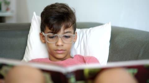 junge lesen buch auf sofa - lesen stock-videos und b-roll-filmmaterial