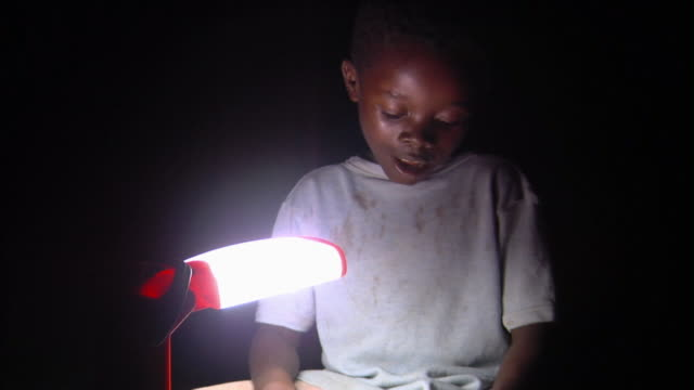 SLO MO MS Boy reading by desk lamp at night, Tamale, Ghana