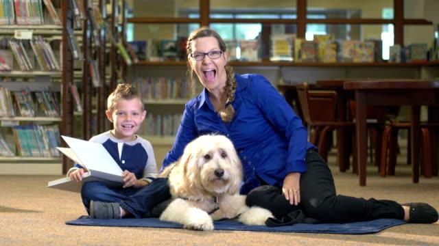 Jongen lezen in bibliotheek met therapie hond