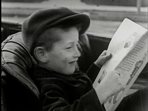 ms, b/w, boy (4-5) reading magazine sitting in vintage car, usa - magazine publication stock videos & royalty-free footage