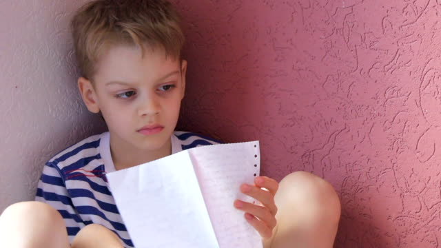 boy reading text on paper