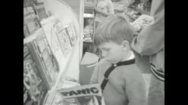 a boy reads panic magazine in the late 1960's - kiosk stock-videos und b-roll-filmmaterial