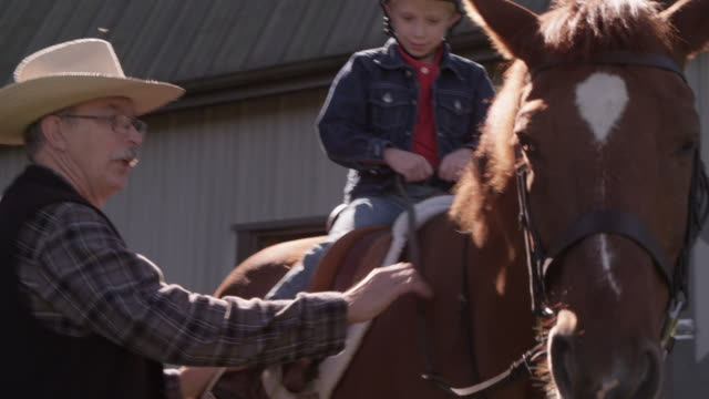 a boy receive instruction as he learns to ride a horse. - pferdestall stock-videos und b-roll-filmmaterial