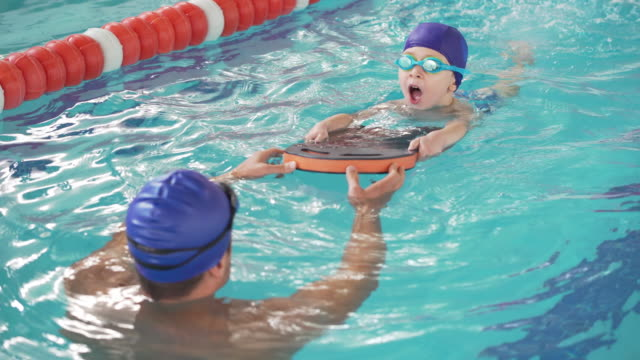 a boy receiving swimming lessons - swimming stock videos & royalty-free footage