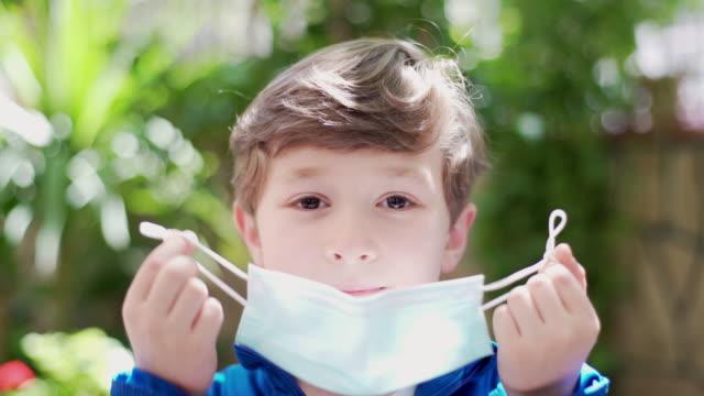 vídeos de stock, filmes e b-roll de menino removendo uma máscara cirúrgica - despindo se