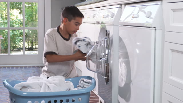 MS Boy (8-9) removing laundry from washing machine to laundry basket, Phoenix, Arizona, USA