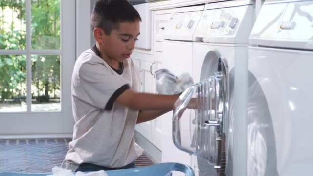 ms boy (8-9) removing laundry from washing machine to laundry basket, phoenix, arizona, usa - chores stock videos & royalty-free footage