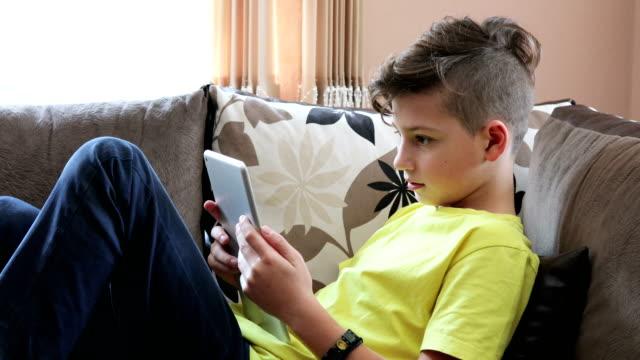 vídeos de stock, filmes e b-roll de menino descansando em casa sobre tablet digital - 12 13 anos