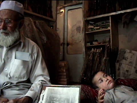 stockvideo's en b-roll-footage met ms boy resting in father's shop grandfather watching darrah in swat agency of tribal zones federally administered tribal areas pakistan audio - vuurwapenwinkel