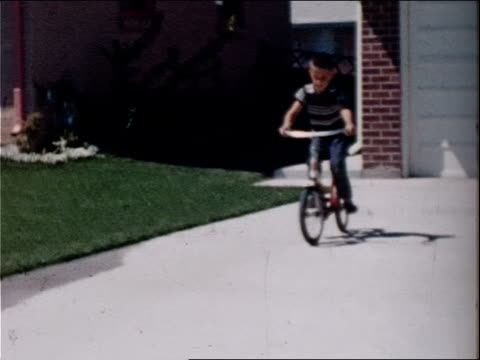 vídeos y material grabado en eventos de stock de a boy rides a bicycle on a sidewalk. - bicicleta vintage