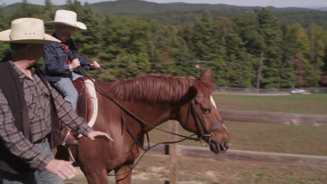 a boy rides a horse beside his instructor. - animal harness stock videos and b-roll footage