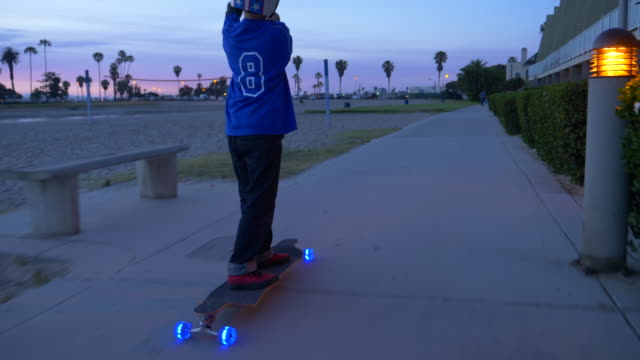 A boy rides a skateboard with led lights wheels in a neighborhood and a sup paddle stick.