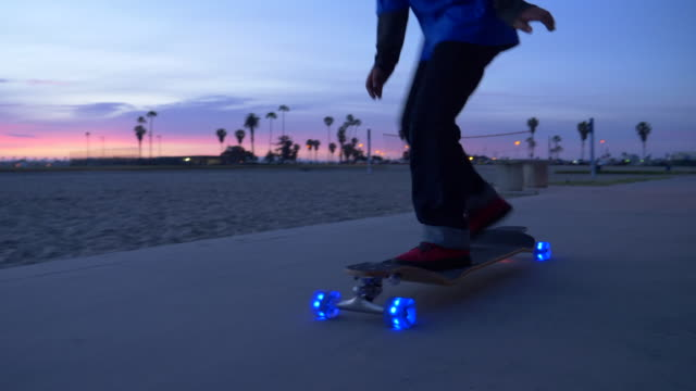 a boy rides a skateboard with led lights wheels in a neighborhood. - grau stock-videos und b-roll-filmmaterial