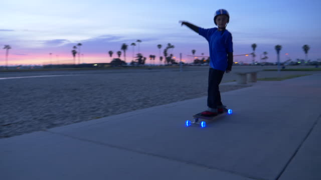 a boy rides a skateboard with led lights wheels in a neighborhood. - zahl 8 stock-videos und b-roll-filmmaterial