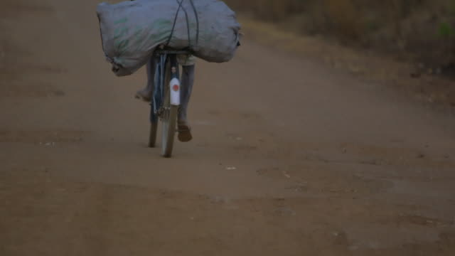 Boy rides bicycle down busy road in Angola