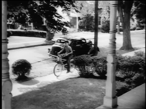 B/W 1943/44 PAN boy rides bicycle + throws newspaper on porch of suburban house / Springfield, NJ