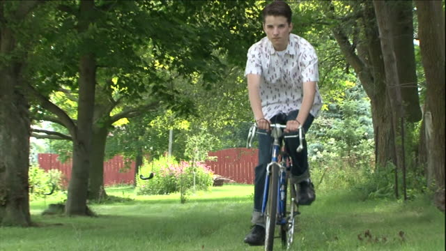 a boy rides his bicycle through a grassy park then stops to fix the chain. - repairing stock videos & royalty-free footage