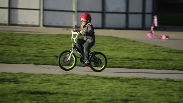 a boy riding a bike in a park. - model released - 1920x1080 - hd - fahrzeug fahren stock-videos und b-roll-filmmaterial