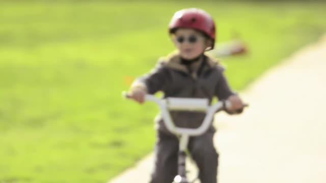 a boy riding a bike in a park. - model released - 1920x1080 - hd - スポーツヘルメット点の映像素材/bロール