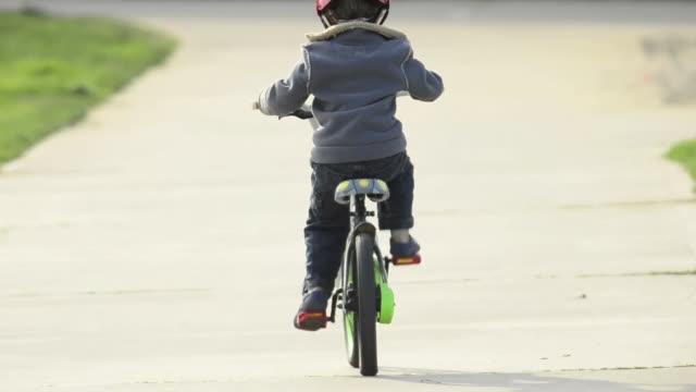 vídeos y material grabado en eventos de stock de a boy riding a bike in a park. - model released - 1920x1080 - hd - un solo niño