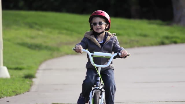 A boy riding a bike in a park. - Model Released - 1920x1080 - HD