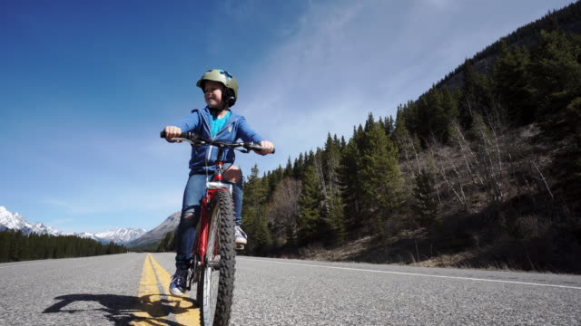boy riding a bike in the sun, towards mountains - cycling helmet stock videos & royalty-free footage