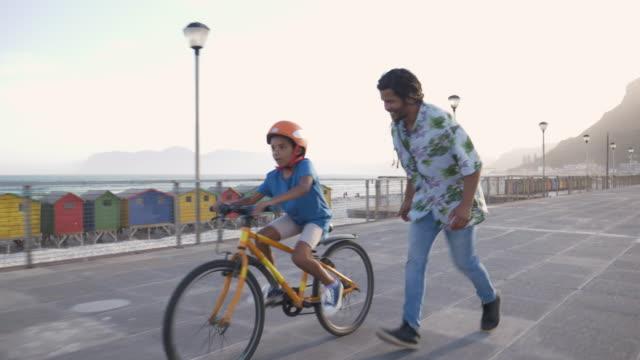 vídeos de stock, filmes e b-roll de boy riding a bike with his dad - teaching