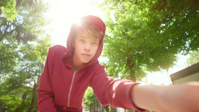vídeos de stock, filmes e b-roll de slo mo ts menino que monta um skate abaixo da rua na luz do sol e que olha na câmera - meninos adolescentes