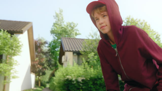 slo mo ts boy auf einem skateboard lächelnd in die kamera - männlicher teenager stock-videos und b-roll-filmmaterial