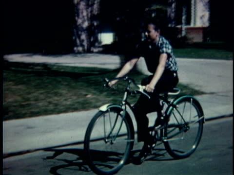WS TS Boy riding bicycle down street / USA