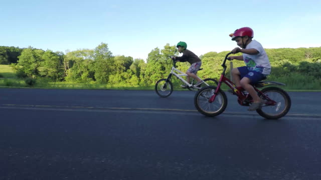 boy riding bicycle on a country road - cycling helmet stock videos & royalty-free footage